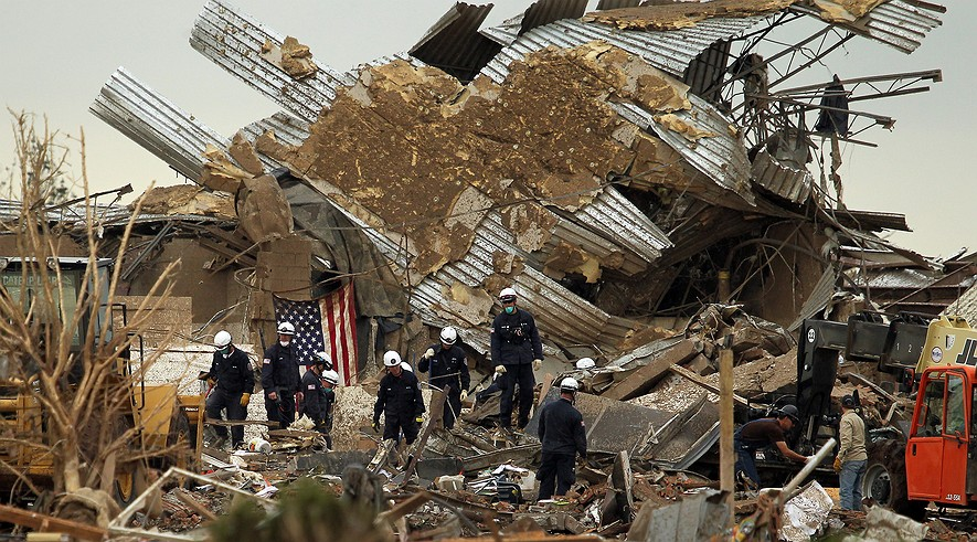 Urban Search and Rescue workers comb through debris, Tuesday, May 21, 2013, at Plaza Towers Elementary School following a massive tornado that hit Moore, Oklahoma.