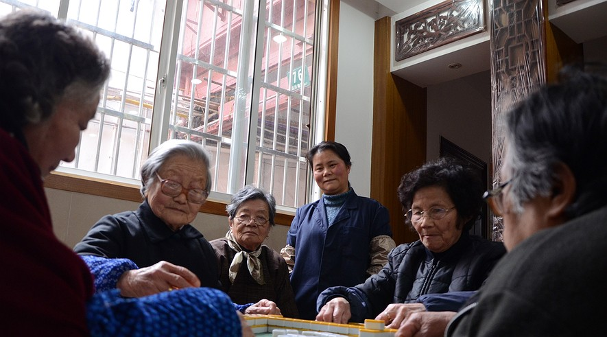 """They call themselves """"orphan grandparents"""" -- elderly people whose grown children have left for jobs in other cities, putting stresses on China's traditional three generation households. Here, a group of elderly women meet for a game of mahjong at the Xintu Center for Health Promotions in Shanghai."""