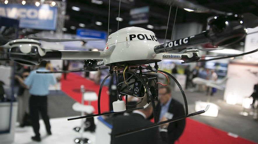 A Microdrones md4-200 unmanned aircraft vehicle hangs above the exhibition floor at the Association for Unmanned Vehicle Systems International conference in Washington, D.C., on Aug. 13, 2013. AUVSI is the world's largest nonprofit organization devoted to advancing the drone and robotics community.