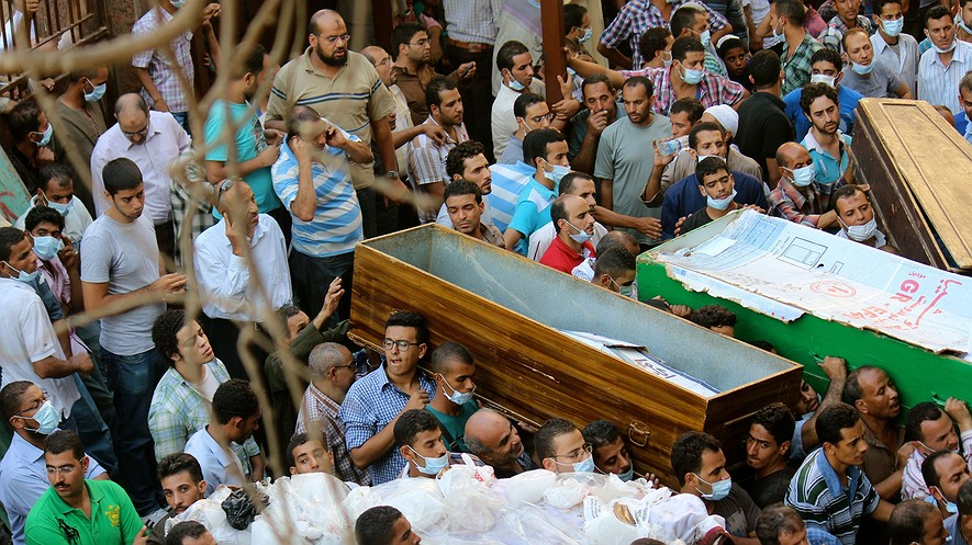 Residents try to move their dead into the overwhelmed Zeinhoum mosque in Cairo in an effort to get them outside of the heat, Thursday, Aug. 15, 2013, a day after the military's crackdown on sit-in sites.