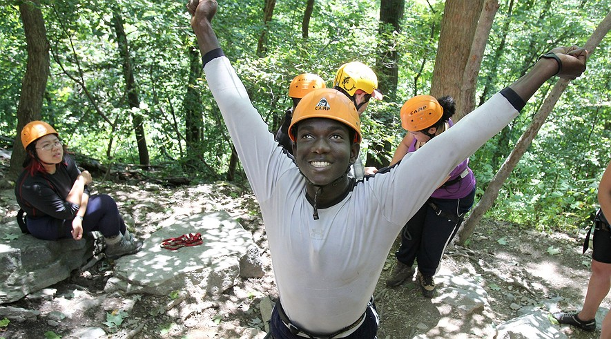 Salomon Andre raises his hands as the first in his group to volunteer for rock climbing during a program for Philadelphia youth. Called Summer Search, the program gives disadvantaged teens a chance to push themselves and gain confidence.