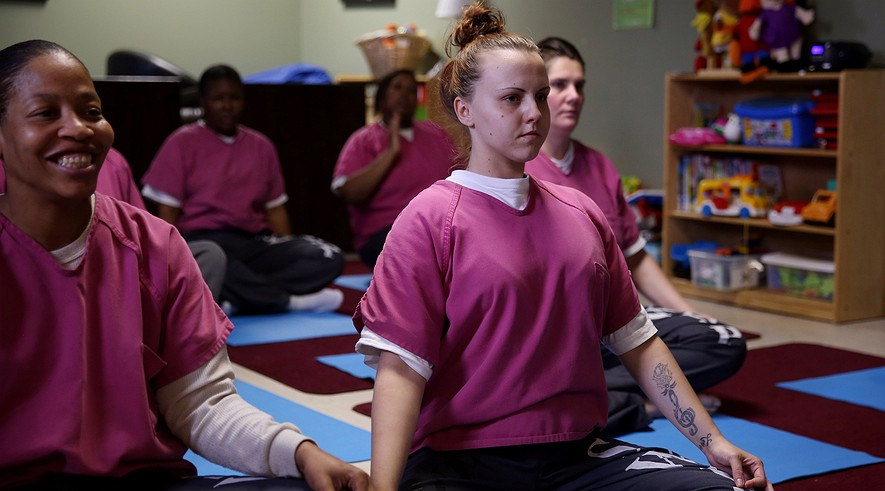 Magdalena Sluzala, right, who is part of the Sheriff's Women's Justice Program, holds a yoga pose during a session with other inmates at the Cook County Jail in Chicago, Illinois, on July 26, 2013.