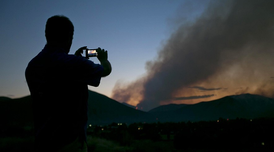 Darin D. Sales of Hailey, Idaho, takes photos of the Beaver Creek Fire looming above the Wood River Valley town, Saturday, Aug. 17, 2013.