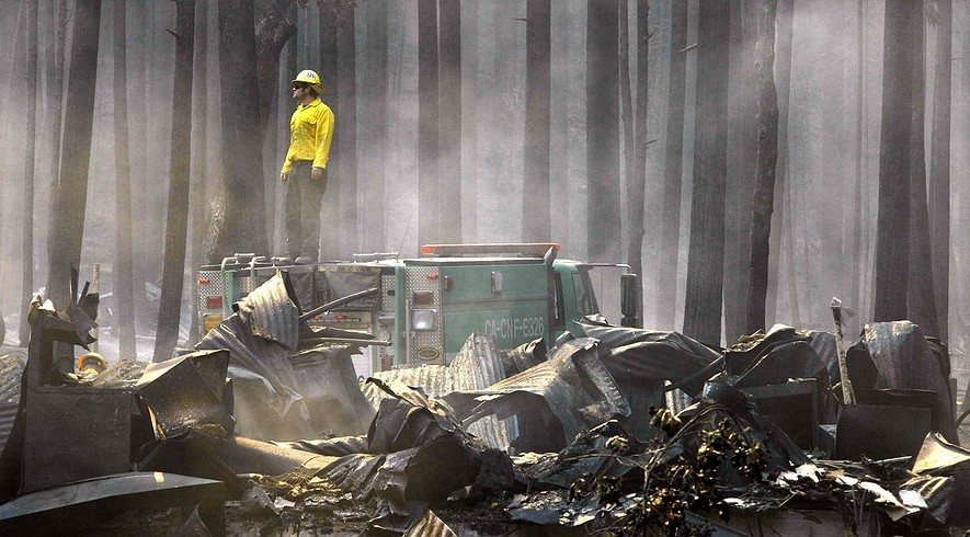 A firefighter surveys the smoldering ruins of the Berkeley Tuolumne Camp near Groveland, California, on Monday, Aug. 26, 2013.