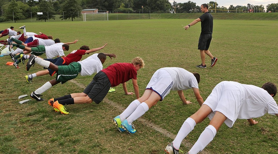 Trainer Eric Lay watches as the junior varsity soccer team goes through conditioning drills at school in Ladue, Mo., on Oct. 2, 2013.