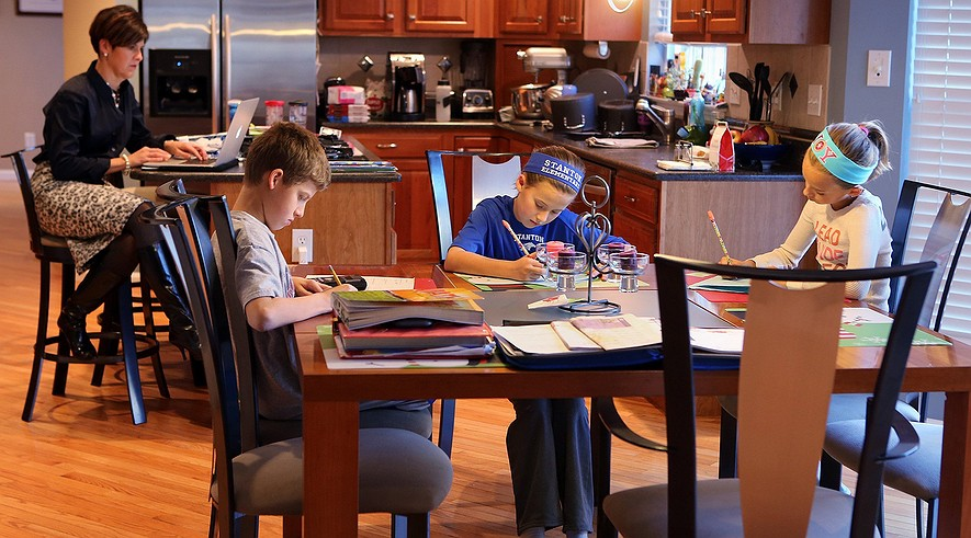 Sixth-grader Kyle Stilwell, 12, (second from left) and his sisters, (from left) fifth-grader Danika, 11, and fourth-grader Natalie, 9, do their homework in Fenton, Mo. Their mom, Niki Stilwell, (left) works from home.