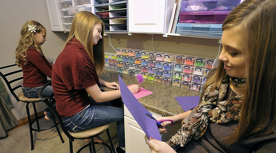 Kelsey Hooten, 16, (right) works on an art project with sisters Hannah, 11, (left) and Lexie, 14, at home in Dayton, Ohio, on Nov. 15, 2013. Because of bullying at school, Kelsey enrolled in an online school. All three sisters attend the online school at different grade levels.