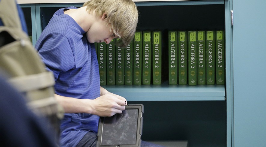 A high school student adjusts a tablet device in an algebra II class at Flower Mound High School in Flower Mound, Texas.