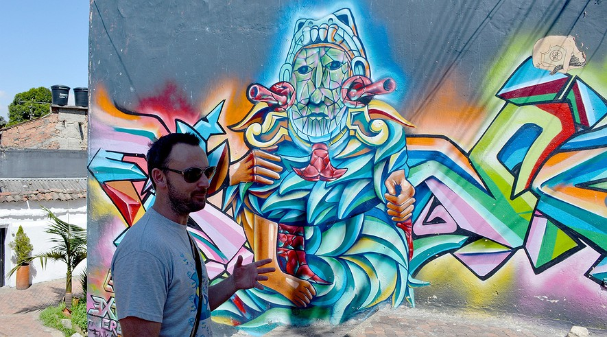 Australian graffiti artist Christian Petersen offers guided tours of the booming street-art scene in Bogota, Colombia. Here, he stands in front of the work of Mexican artist Frank Salvador.