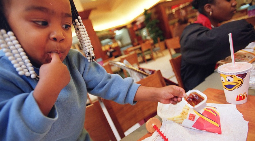 Daijah Mack, 2, of Detroit, Mich., enjoys a side of barbecue sauce with McDonald's french fries. Experts say half of advertising aimed at kids is for food, and 4 of 5 of those ads are for sugary cereal, soft drinks, fast food or salty snacks.