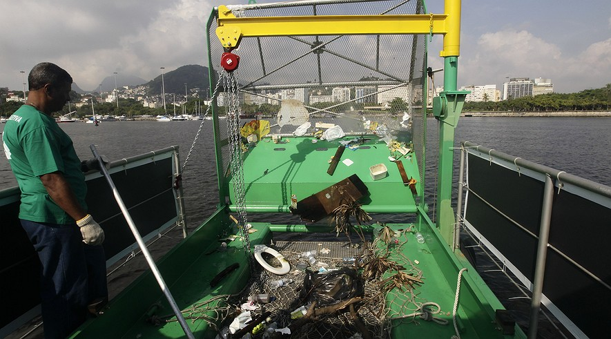 A worker stands next to trash collected by a garbage-collecting barge on Guanabara Bay in Rio de Janeiro, Brazil, Monday, Jan. 6, 2014. Levels of fecal coliforms are so high that nearly all the beaches that dot the 148-square-mile (383-square-kilometer) bay have long been abandoned, and some observers have warned of possible heath risks to athletes who come in contact with the water.