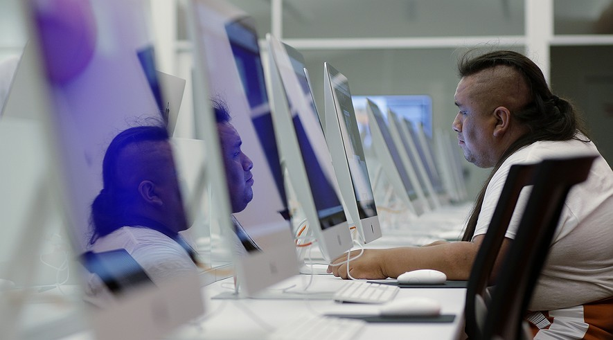 """Paco Garcia is reflected on computer screens as he uses a computer at BiblioTech, a first of its kind digital public library, on Sept. 16, 2013, in San Antonio, Texas. BiblioTech is a play on the Spanish word for library which is """"biblioteca."""""""