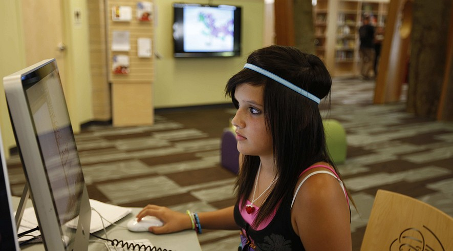 Alejandra Delacruz, 11, does homework, watches YouTube and checks her Facebook account at a library in Denver, Colo. A new study shows that peoples' moods and emotions can be contagious through the social networking site.