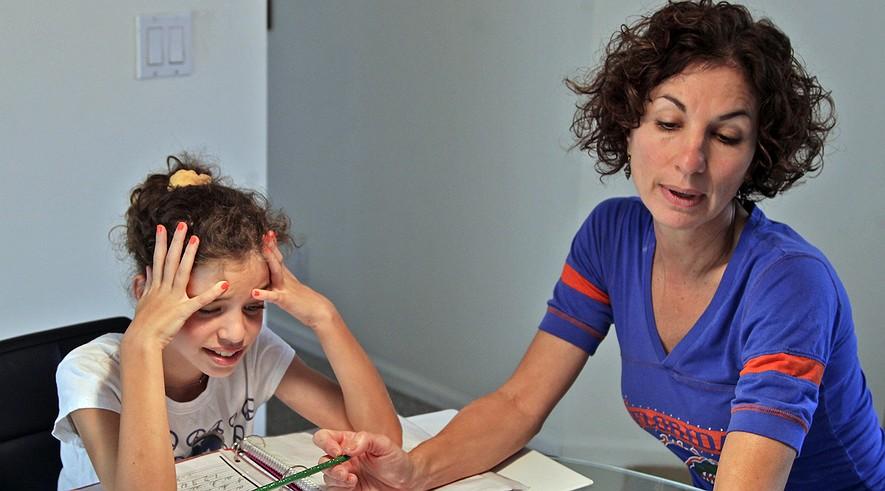 Haley Regent (left) shows her frustration while doing her math homework with her mother, Debbie Regent. Weston, Fla.,resident Debbie Regent, 48, a working parent with two girls, supervises her children's homework for several hours.