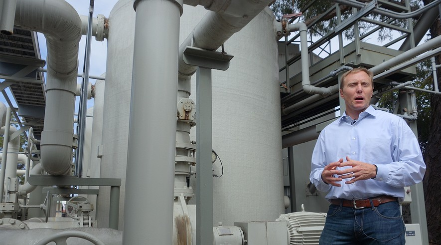 In this April 25, 2014, photo, Joshua Haggmark, interim resources manager for Santa Barbara, California, stands next to a desalination plant, which removes salt from ocean water, in Santa Barbara. The city is considering restarting the plant as California withers in a drought.