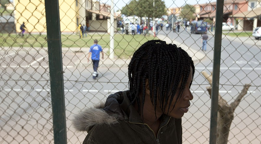 Silla Zelia, 23, an asylum-seeker from Ivory Coast, watches a soccer match at the migrant center in Mineo in Sicily, Italy, April 21, 2015.
