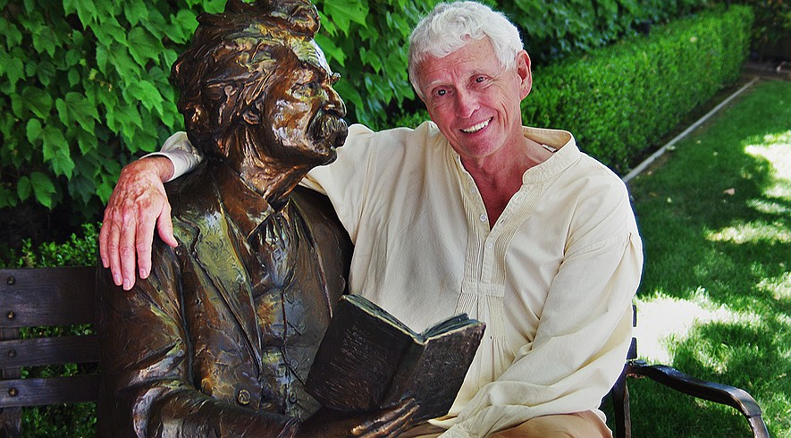 "Jim Fletcher, the ""official storyteller of Calaveras County,"" with a bronze statue of Mark Twain on May 6, 2015, at Camps Restaurant in Angels Camp, California, where he gives a weekly presentation on Twain's mining days in California."
