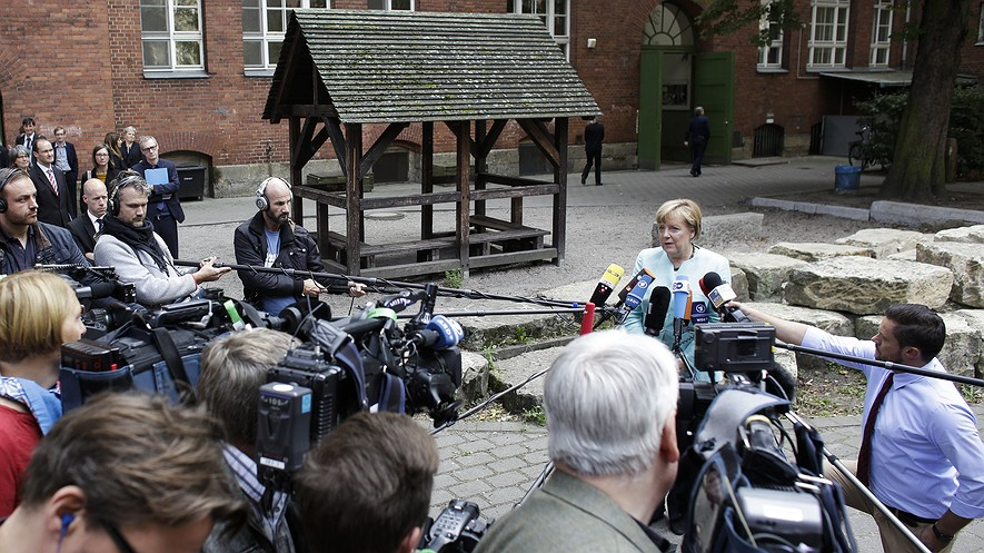 """German Chancellor Angela Merkel (right) speaks to the media after visiting a """"Welcome Class,"""" a special school class for migrants and refugees at the Ferdinand-Freiligrath school in Berlin, Germany, Sept. 10, 2015."""