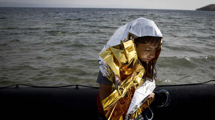 A young Syrian boy is wrapped with a thermal blanket as he arrives with others at the coast of the island of Lesbos, Greece, on a dinghy after crossing from Turkey, Sept. 7, 2015. The island of  100,000 residents has been transformed by the sudden new population of 20,000 refugees and migrants, mostly from Syria, Iraq and Afghanistan.