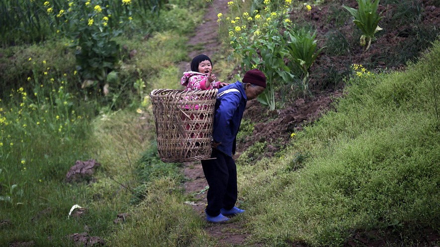 A Chinese woman caries a baby in a traditional basket on the outskirts of Chongqing, China, March 19, 2013..