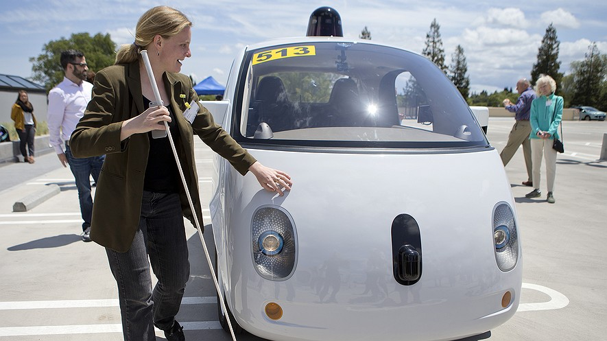 Jessie Lorenz of the Independent Living Resource Center in San Francisco, California, who is blind, touches the two-seater prototype of Google's self-driving car at Google headquarters in Mountain View, California, May 13, 2015.