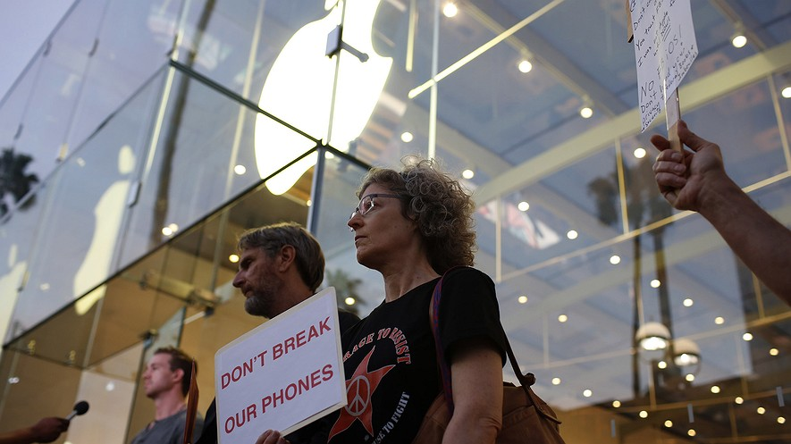 Protesters, including Victoria Best (right) and Charles Fredricks, hold signs supporting Apple in its fight against the FBI. They stood outside the Apple store in Santa Monica, California, on Feb. 23, 2016.