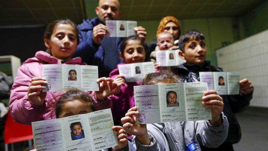 "Wafy Al-Hamoud Alkhaldy (center, back row), his wife, Asma Al Saleh, (to his left) and their six children, from the eastern Syrian town of Deir ez-Zor, present their newly issued ""Ankunftsnachweis,"" an initial German registration document for migrants, following their registration at the former British Harewood barracks in Herford, Germany, Feb. 22, 2016."
