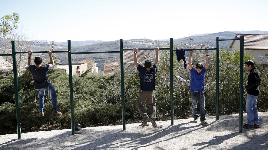 Students do pull-ups as they train at the Bnei David academy in Israel. Photo: REUTERS/Ronen Zvulun. BOTTOM: Seventeen-year-old Langley High School junior Andrew Shapiro shattered three Guinness World Records over the weekend at a fundraiser for the American Cancer Society in Virginia.