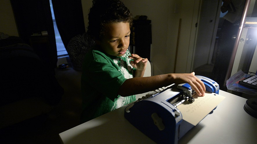Second-grader Amare Leggette, of Eastover, North Carolina, checks the vocabulary words he wrote on his braille writer on May 31, 2016. Amare, who is blind, is heading to the national finals of the Annual Braille Challenge on June 18.