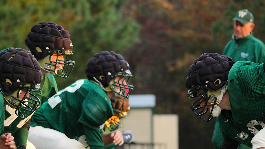 The Wesleyan School football team in Norcross, Ga., at practice wearing Guardian helmet caps to minimize the impact of head collisions on the field.