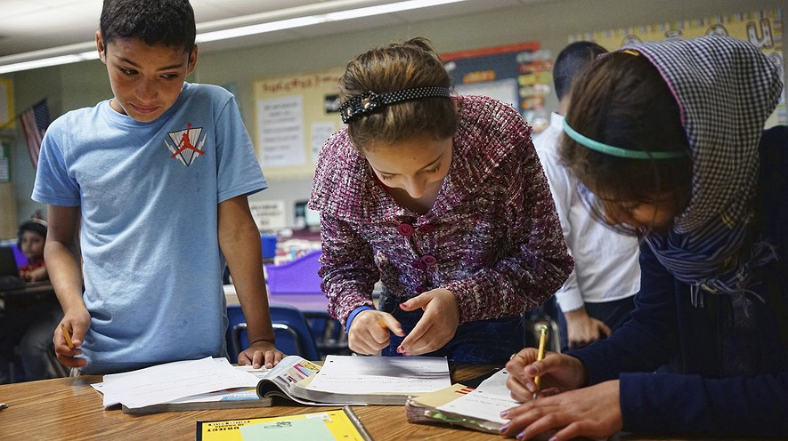 Abdulhamid Ashehneh, 12, (left) works on English language exercises with fellow students in a class filled with refugee children at Cajon Valley Middle School in El Cajon, California, October 4, 2016.