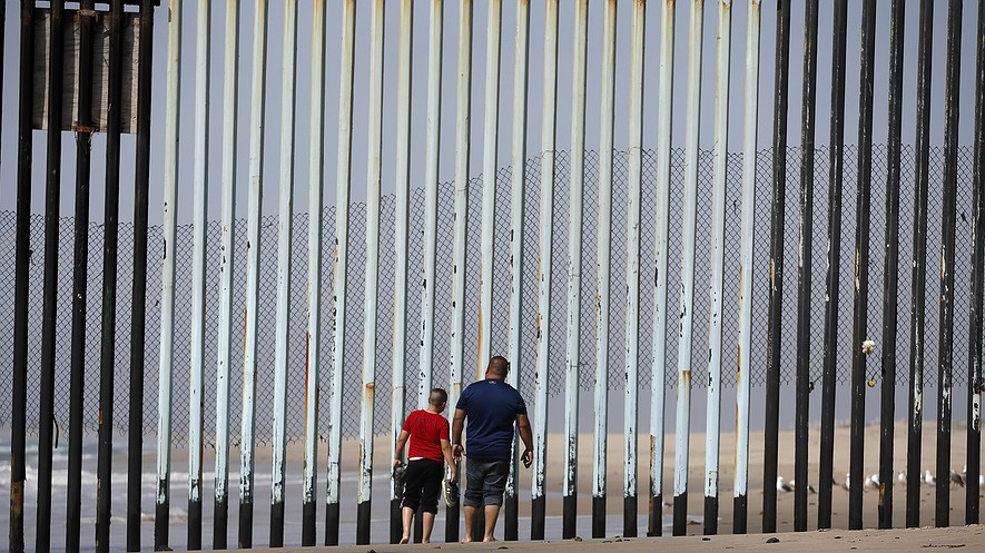 In this March 2016 file photo, two people walk toward metal bars marking the United States border where it meets the Pacific Ocean in Tijuana, Mexico. U.S. President Donald Trump will direct the Homeland Security Department to start building a wall at the Mexican border. Photo: AP/Gregory Bull