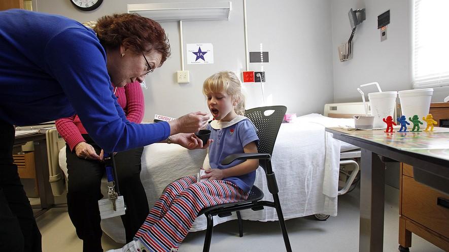 Hanna Carter, de 5 años (derecha) de Roanoke, Virginia, toma una dosis de proteína de maní de Pam Steele, una enfermera de la Duke South Clinic de Duke University en Durham, Carolina del Norte, 10 de marzo de 2009.