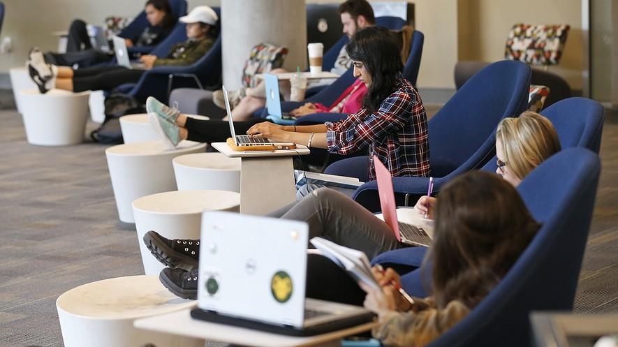 Los estudiantes se sientan mirando hacia el campus mientras trabajan en sus computadoras en la biblioteca renovada James Branch Cabell Library en el campus de la universidad de Virginia Commonwealth University en Richmond, Virginia.