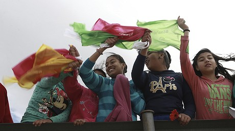 """Young people wave colored flags reading """"Peace"""" as they form a symbolic human wall along the Rio Grande, which marks the border between Mexico and the United States, in Ciudad Juarez, February 17, 2017. Responding to plans by President Donald Trump to build a wall along the length of the U.S.-Mexico border, more than a thousand people lined the Mexican bank of the Rio Grande in Ciudad Juarez, holding hands and carrying flowers. AP Photo/Christian Torres"""