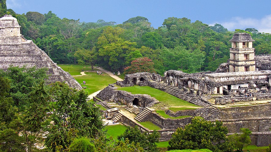 "The Maya site of Palenque viewed from the Temple of the Cross. The palace complex is to the right and the Temple of Inscriptions is to the left. Palenque is a Spanish word for ""fortification."" An ancient name for the city was Lakam Ha, which translates as ""Great Water,"" for the springs and small rivers which flow from the site. Photo by: Dennis Jarvis via Wikimedia."