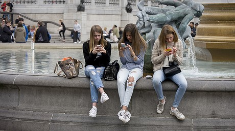 In a main square in London, England, three teenagers tweet and message their friends, unaware of their surroundings and absorbed in the functions of their devices. Photo by: In Pictures Ltd./Corbis via Getty Images