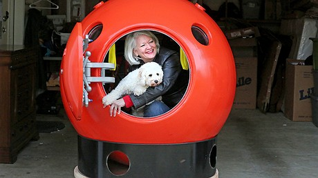 In Ocean Park, on Long Beach Peninsula in Washington state, Jeanne Johnson, with her dog, Trixie, peers out of her two-person tsunami survival pod. The sphere has a hatch with a waterproof seal, and two small windows and two air vents that also can be made watertight. Photo by: Greg Gilbert/Seattle Times/TNS