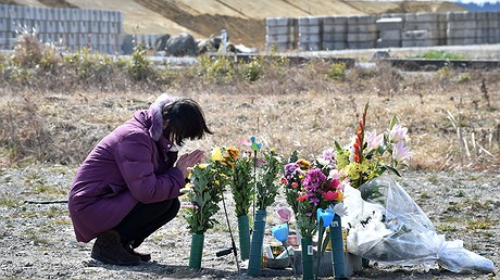 A woman prays for victims on the sixth anniversary of the 2011 quake-tsunami disaster in Namie, a no-entry zone in Fukushima prefecture. Photo by: Kazuhiro Nogi/AFP/Getty Images