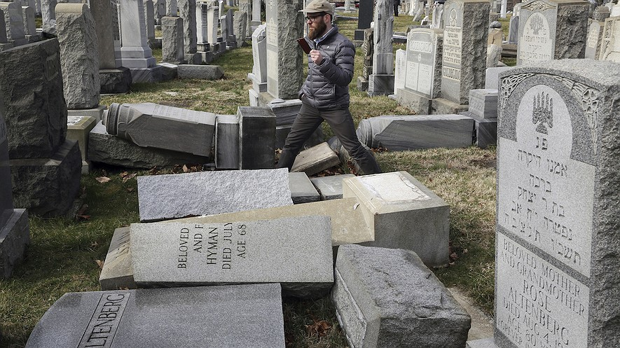 Rabbi Joshua Bolton of the University of Pennsylvania's Hillel center surveys vandalized headstones at Mount Carmel Cemetery on February 27, 2017, in Philadelphia, Pennsylvania. The headstones were damaged less than a week after similar vandalism in Missouri, authorities said. AP Photo/Jacqueline Larma