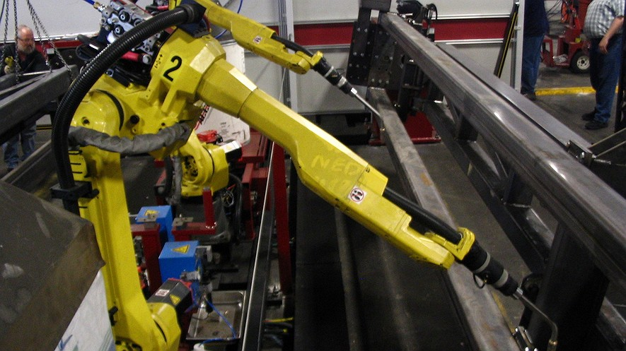 Articulated welding robots, a type of industrial robot, used in a factory. Photo from Wikimedia Commons