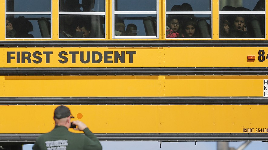 Students watch a police officer investigate their school bus that collided with another bus on January 26, 2017, in Wichita, Kansas. According to police, 27 children suffered minor injuries. Legislative momentum in a number of states is building behind seat belt requirements on school buses. Photo from Travis Heying/Wichita Eagle/TNS
