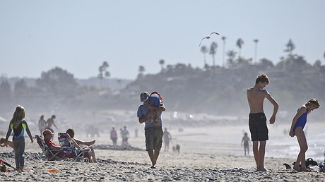 A man carries a young boy over his shoulder as he walks among beachgoers enjoying unusually warm winter temperatures on February 16, 2016, in Encinitas, California. Global warming's milder winters will likely nudge Americans off the couch more in the future, a small benefit of climate change, a new study finds. AP Photo