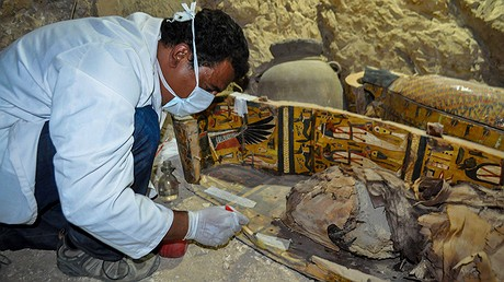 An expert inspects a sarcophagus found with mummies and sculptures inside a grave, which was estimated to be more than 3,500 years old, during archaeological work in Luxor, Egypt, April 18, 2017. Photo by: Stringer/Anadolu Agency/Getty Images