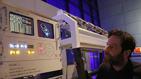 """Artist Nick Ryan poseswith his """"Machine 9,"""" a work of scientific art that transforms the movement of 27,000 tracked space junk objects into sound as they are detected overhead, at the Science Museum in February 2017 in London, England. AP Photo/Alastair Grant"""