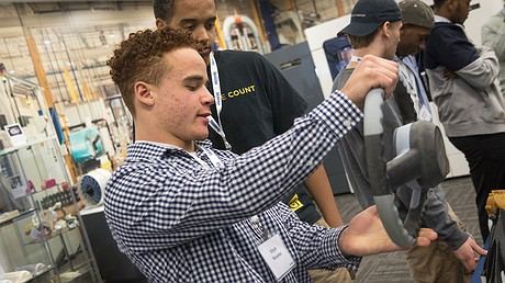 High school student Elijah Rosalez inspects a 3-D printed steering wheel, commenting on how heavy it is. Photo from Matt Weber/Minneapolis Star Tribune/TNS.
