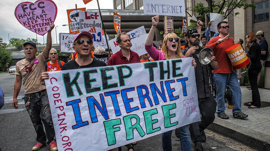 Protesters march past Federal Communications Commission headquarters as the FCC meets to consider a proposal on net neutrality on May 15, 2014, in Washington, D.C. Photo by: Bill O'Leary/The Washington Post via Getty Images