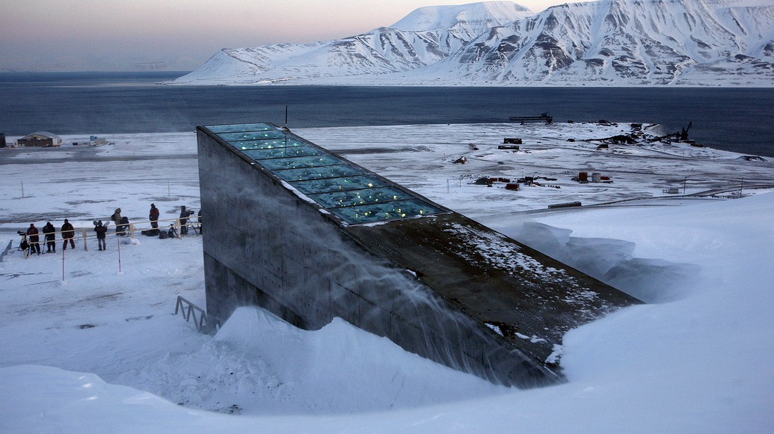 """Snow blows off the Svalbard Global Seed Vault before being inaugurated at sunrise, February 26, 2008. The """"doomsday"""" seed vault built to protect millions of food crops from climate change, wars and natural disasters opened in 2008 deep within an Arctic mountain in the remote Norwegian archipelago of Svalbard. Photo by: AP Photo/John McConnico"""