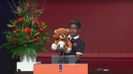 Reuben Paul presents his teddy bear and its technical abilities at a cybersecurity conference. Photo by: Youtube/AFP