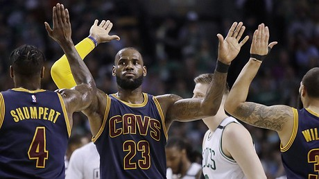 Cleveland Cavaliers forward LeBron James trades high-fives with teammates Iman Shumpert (left) and Deron Williams during the first half of Game 2 of the NBA basketball Eastern Conference finals against the Boston Celtics, May 19, 2017, in Boston, Massachusetts.